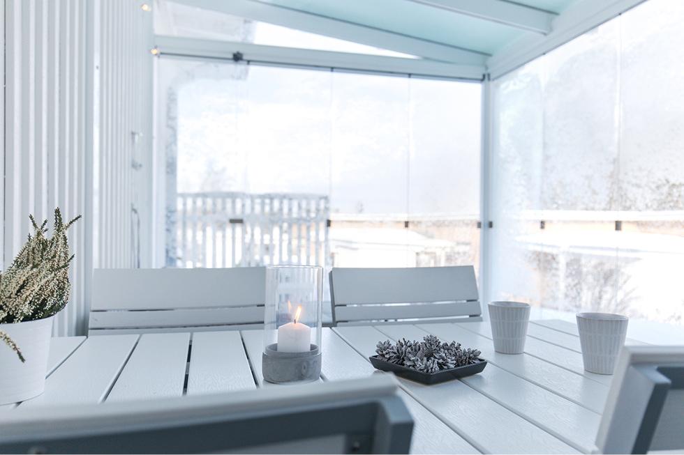 Kynttilä ja käpyasetelma lasitetun terassin pöydällä