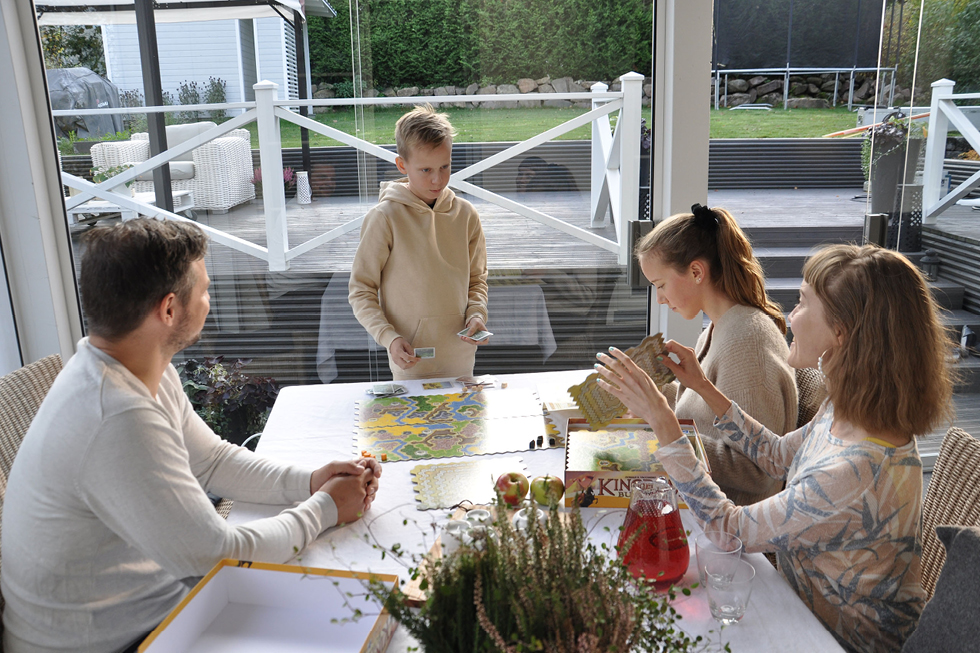 Prhe pelaa lautapeliä lasitetulla terassilla