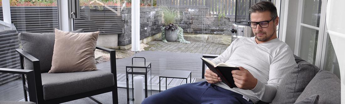 Lasitetulla terassilla mies lukee