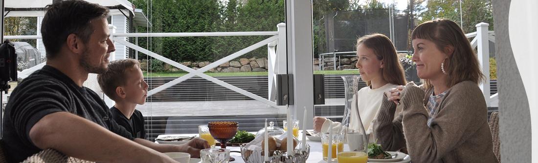 Perhe ruokailee lasitetulla terassilla