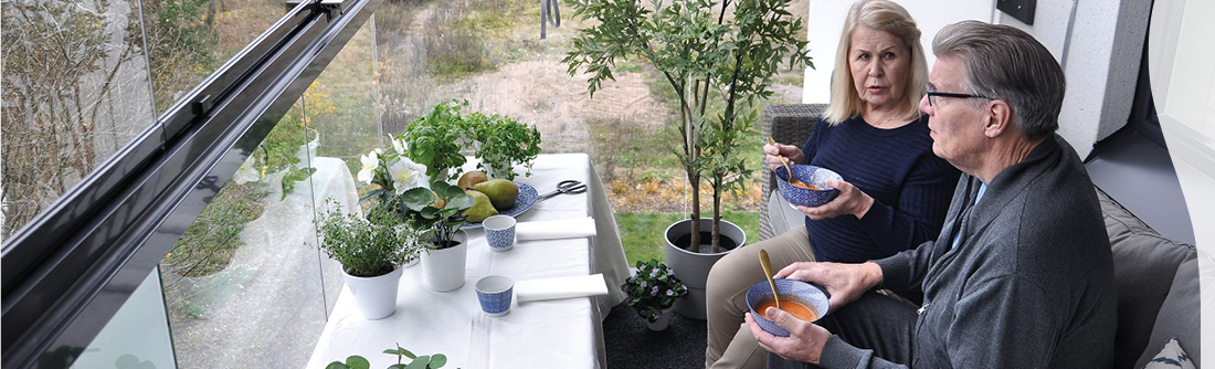 Mies ja nainen ruokailevat lasitetulla parvekkeella
