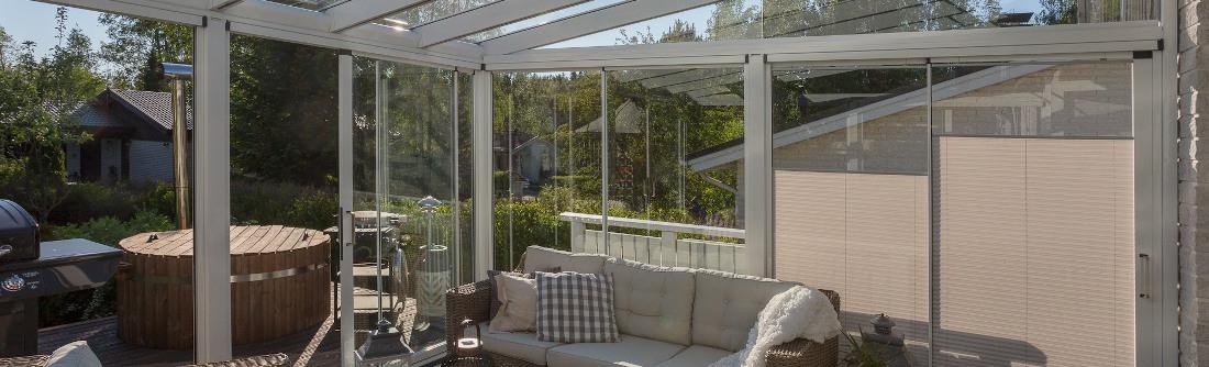 Aurinkoinen lasiterassi, jossa sohva